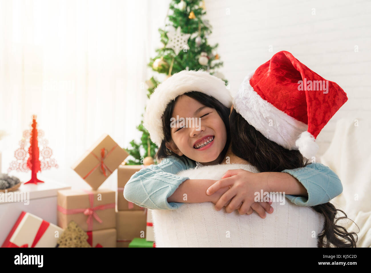 Cute Asian Daughter Girl Give Her A Mother Hug After Exchanging Gifts Parent And Little Child Having Fun Near Tree Indoors Merry Christmas Happy