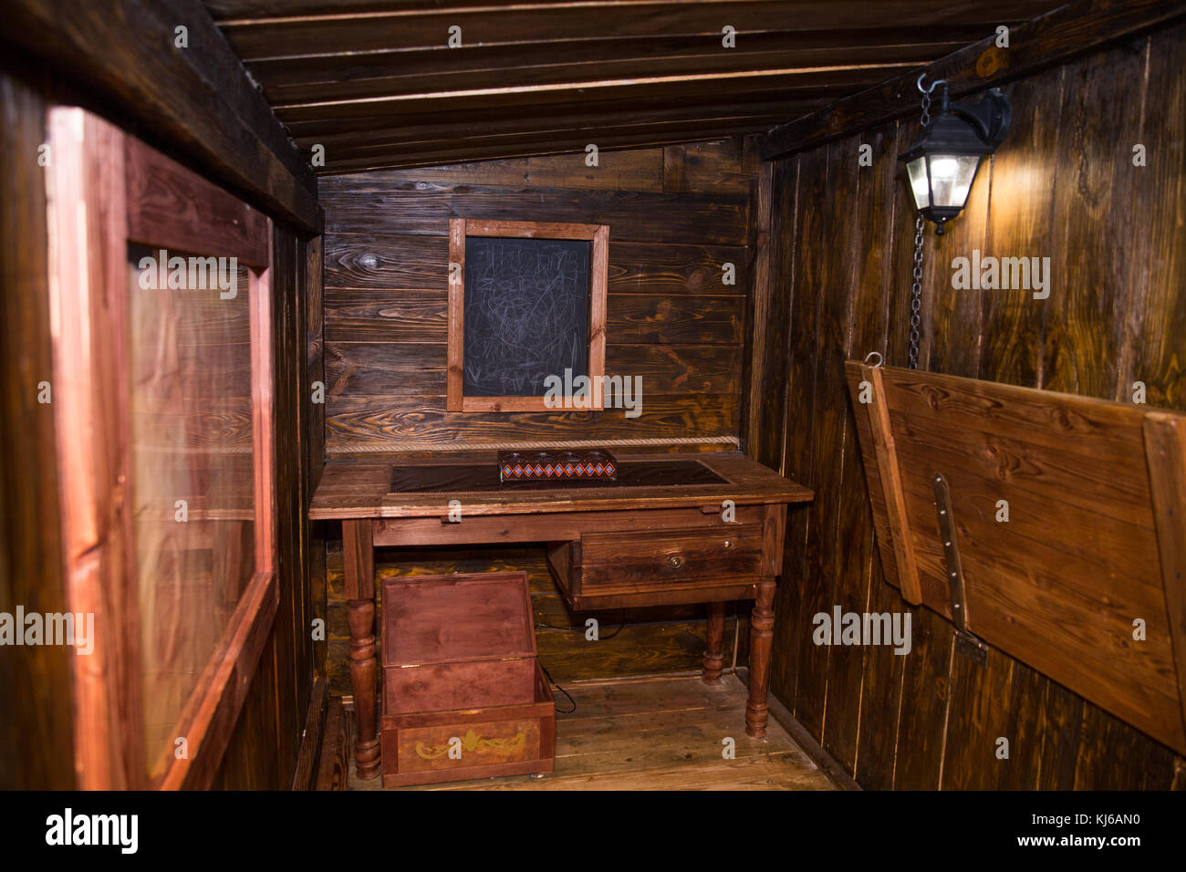 Interior Of Old Ship Cabin With Wooden Panels And Cords Lantern Chest Table Board