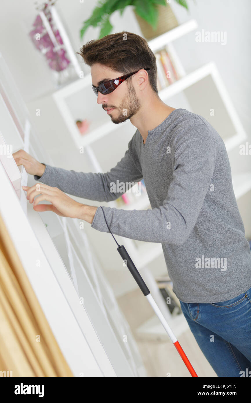 blind man with white stick and dark glasses at home stock photo
