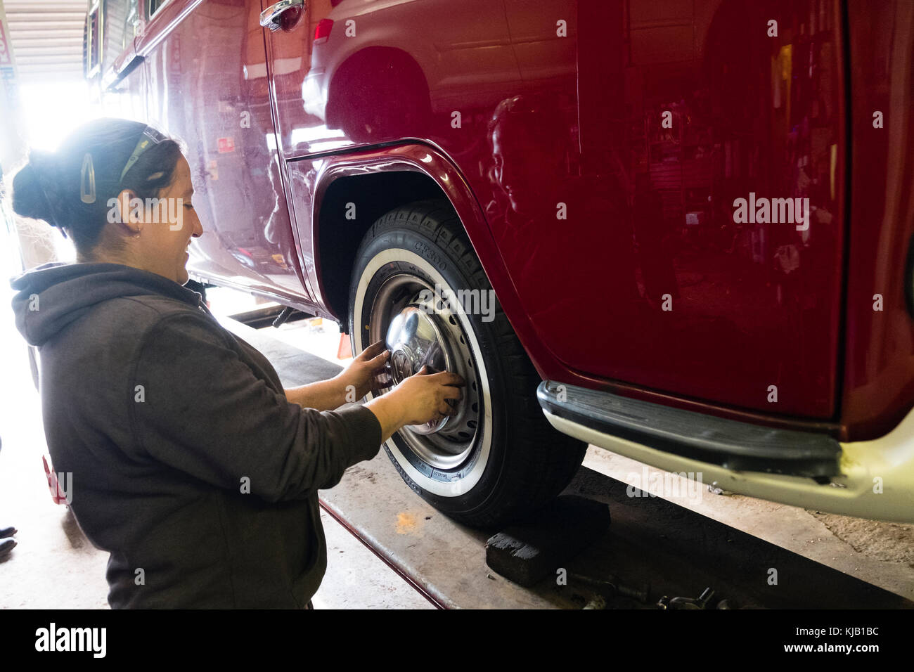 a female mechanic working in a small independent garage workshop replacing the wheels and hub