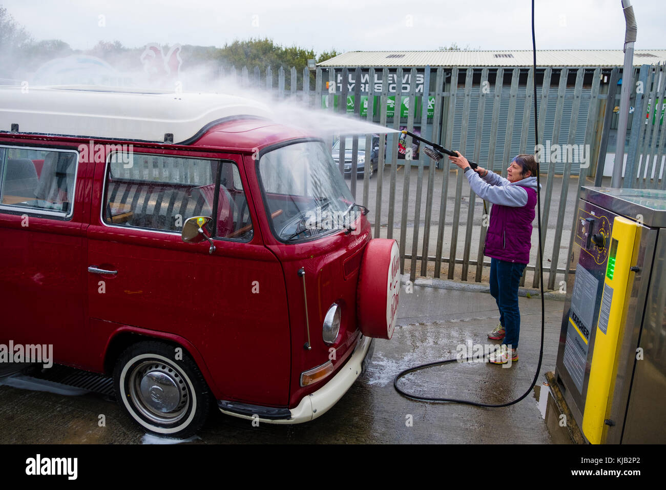A middle aged woman at a self service coin operated car wash a middle aged woman at a self service coin operated car wash washing her classic red volkswagen vw type 2 t2 bay window campervan uk solutioingenieria Image collections