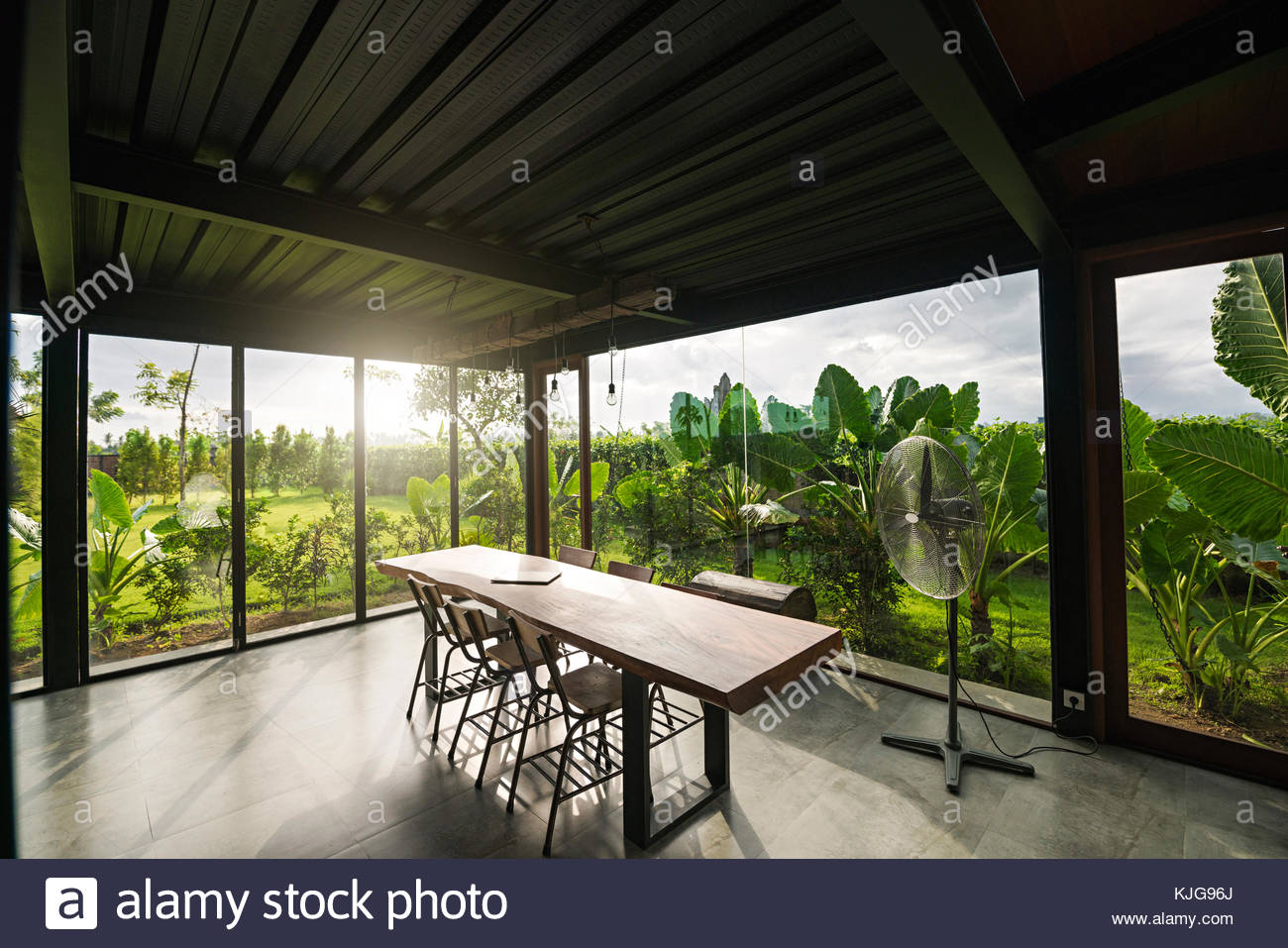 Awesome Modern Wooden Table In Contemporary Design House With Glass Facade  Surrounded By Lush Tropical Garden