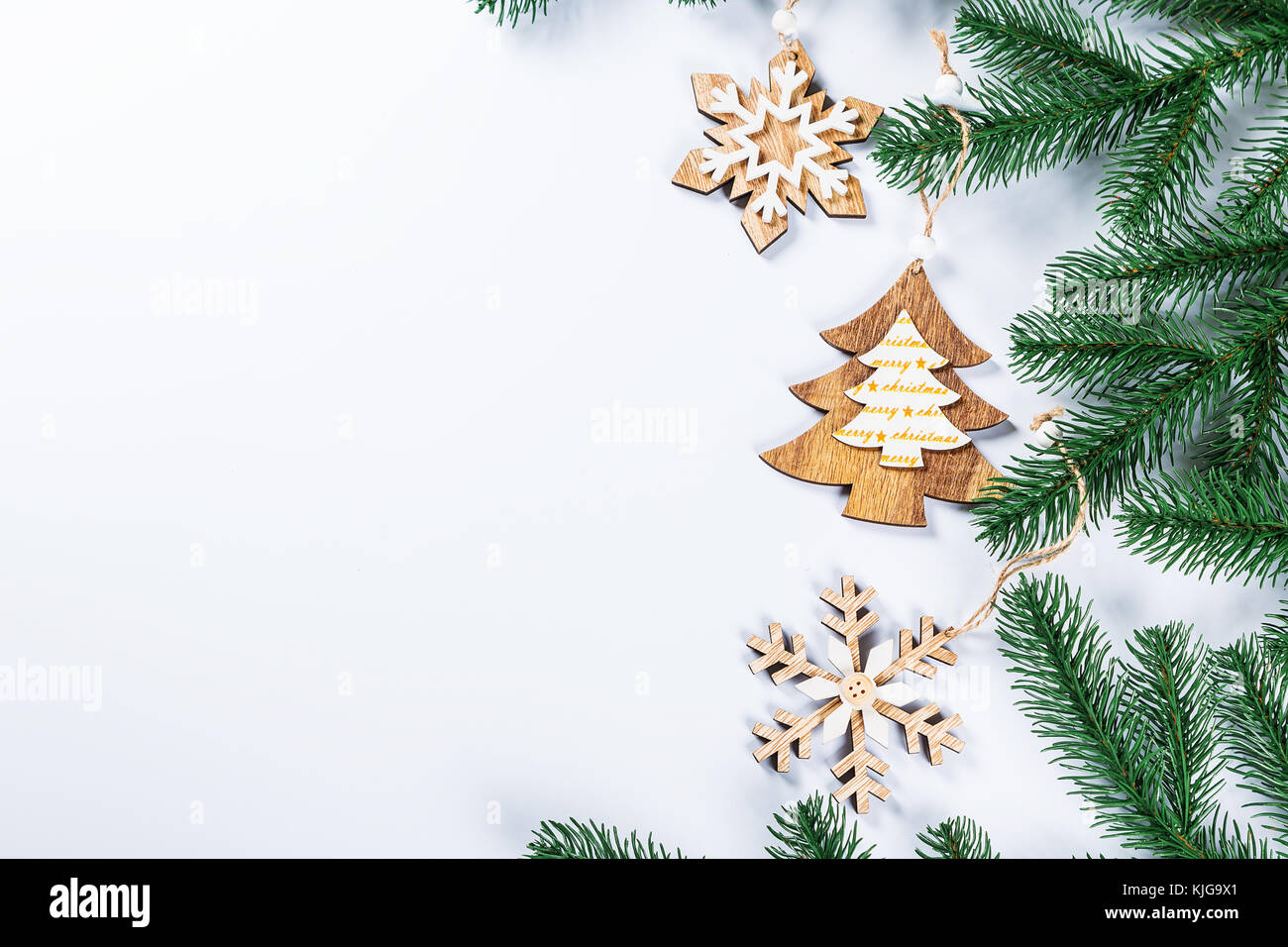 christmas frame with the branches of the christmas tree and wooden decorations on white background simple christmas composition with free space
