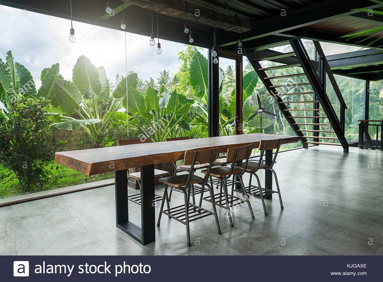 High Quality Modern Wooden Table In Contemporary Design House With Glass Facade  Surrounded By Lush Tropical Garden