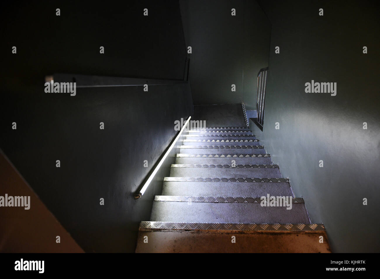 Steep Flight Of Steps In A Dark Shadowy Interior With An Illuminated Hand  Rail And Metal Edged Treads