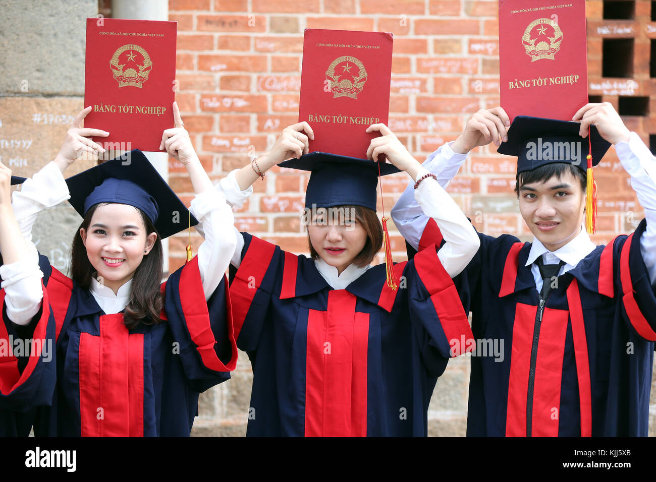 Group of Young Asian university students wearing cap and gown. Ho ...