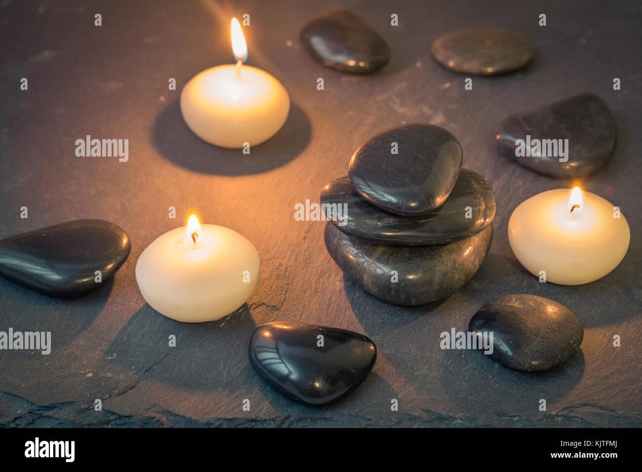 black stones and burning candles on dark background stock photo