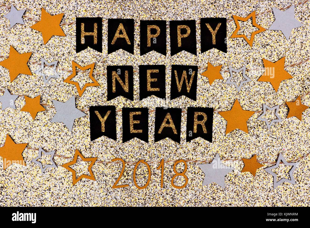 happy new year 2018 banner with strings of gold and silver stars against a glittery gold background