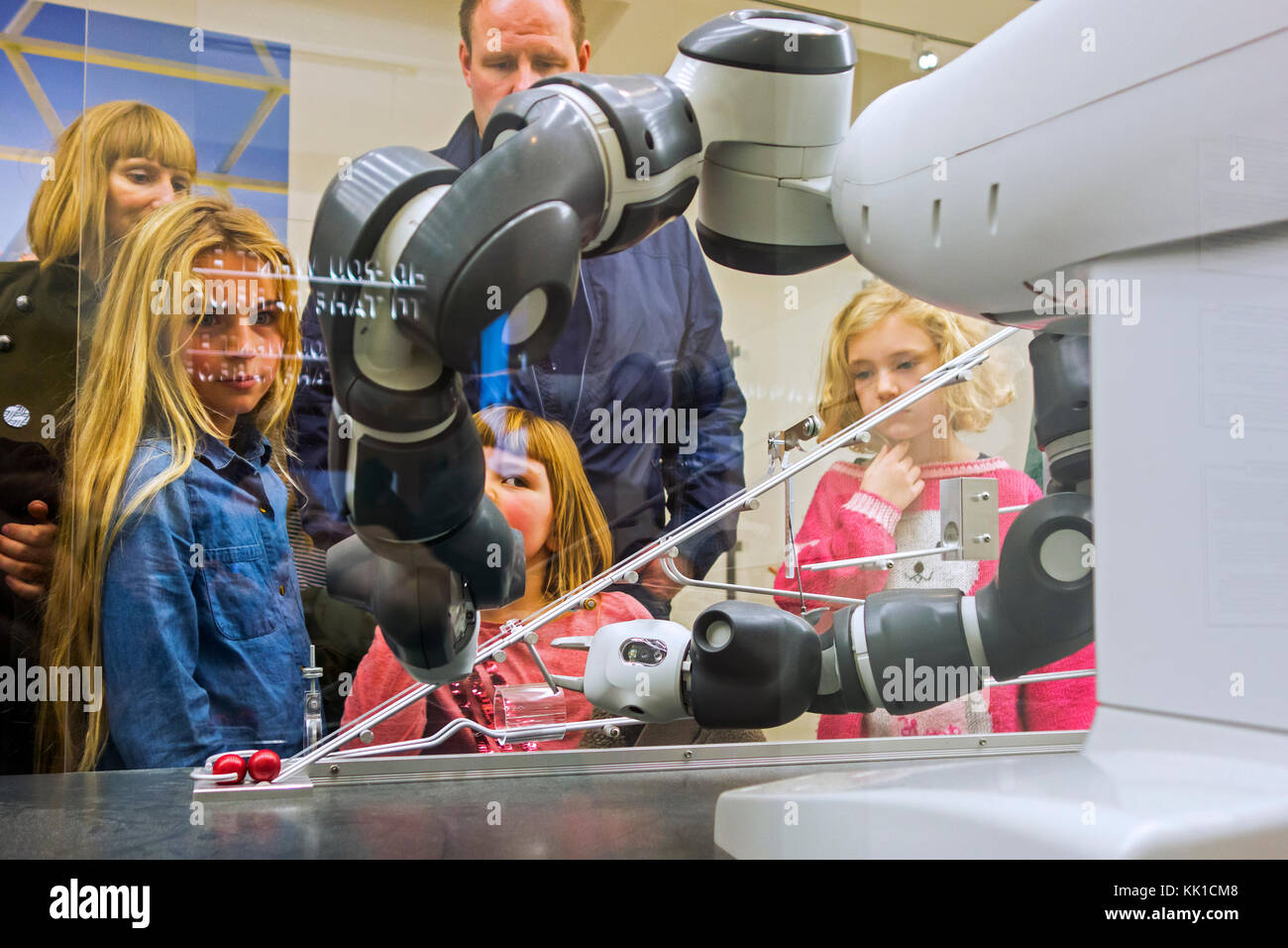 Curious Children Looking At Demonstration With Industrial Robot Arms