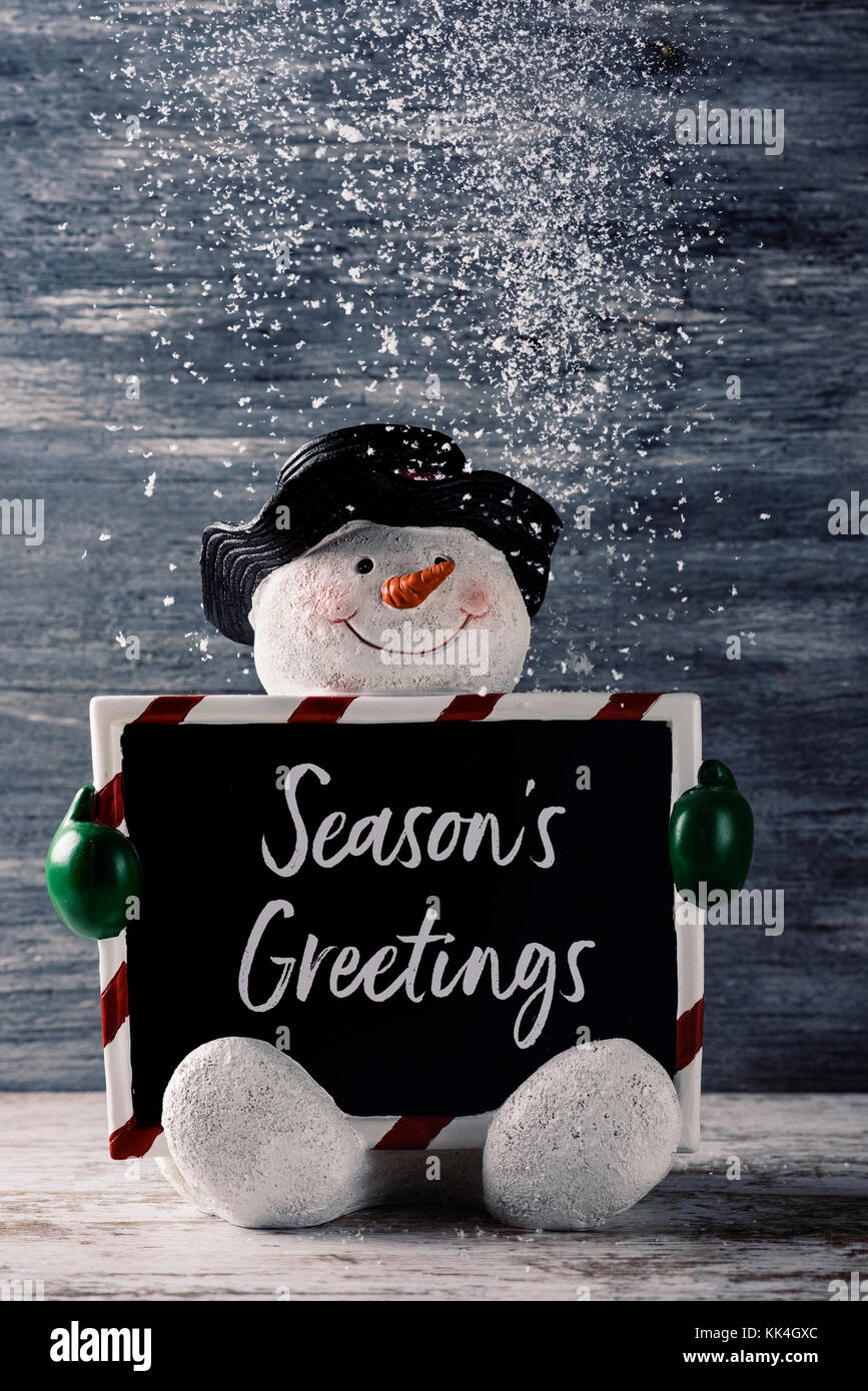 Seasons greetings stock photos seasons greetings stock images alamy a funny snowman holding a black signboard with the text seasons greetings written in it against kristyandbryce Images