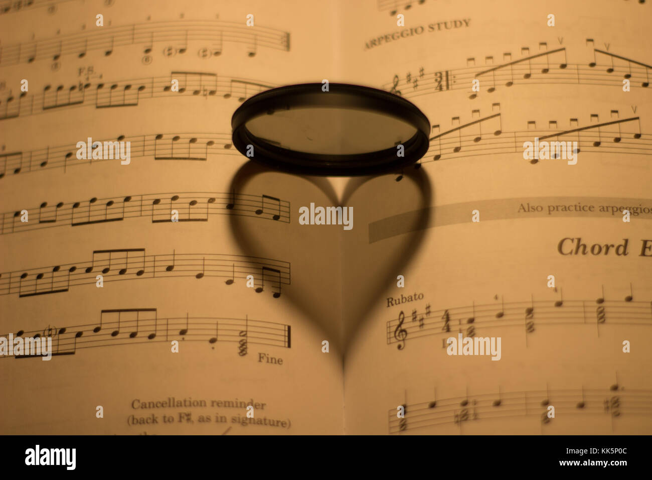 Heart shaped shadow on a vintage music sheet under the light of one heart shaped shadow on a vintage music sheet under the light of one lamp ccuart Image collections
