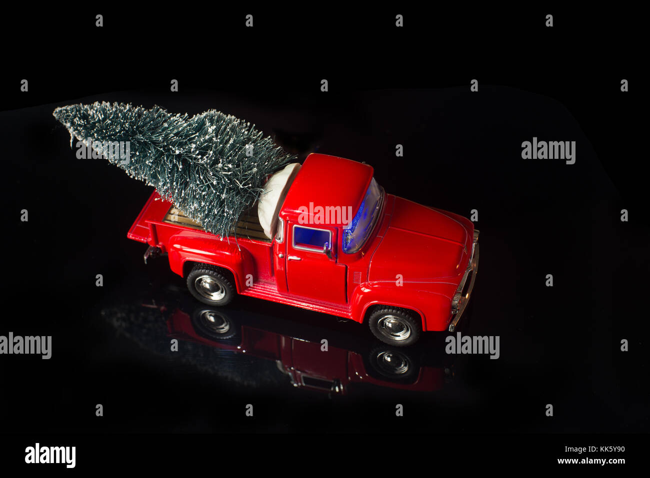 Red Miniature Vintage Truck Deliver Christmas Tree On Its Back Black Background With Reflection Mirror Of The Objects