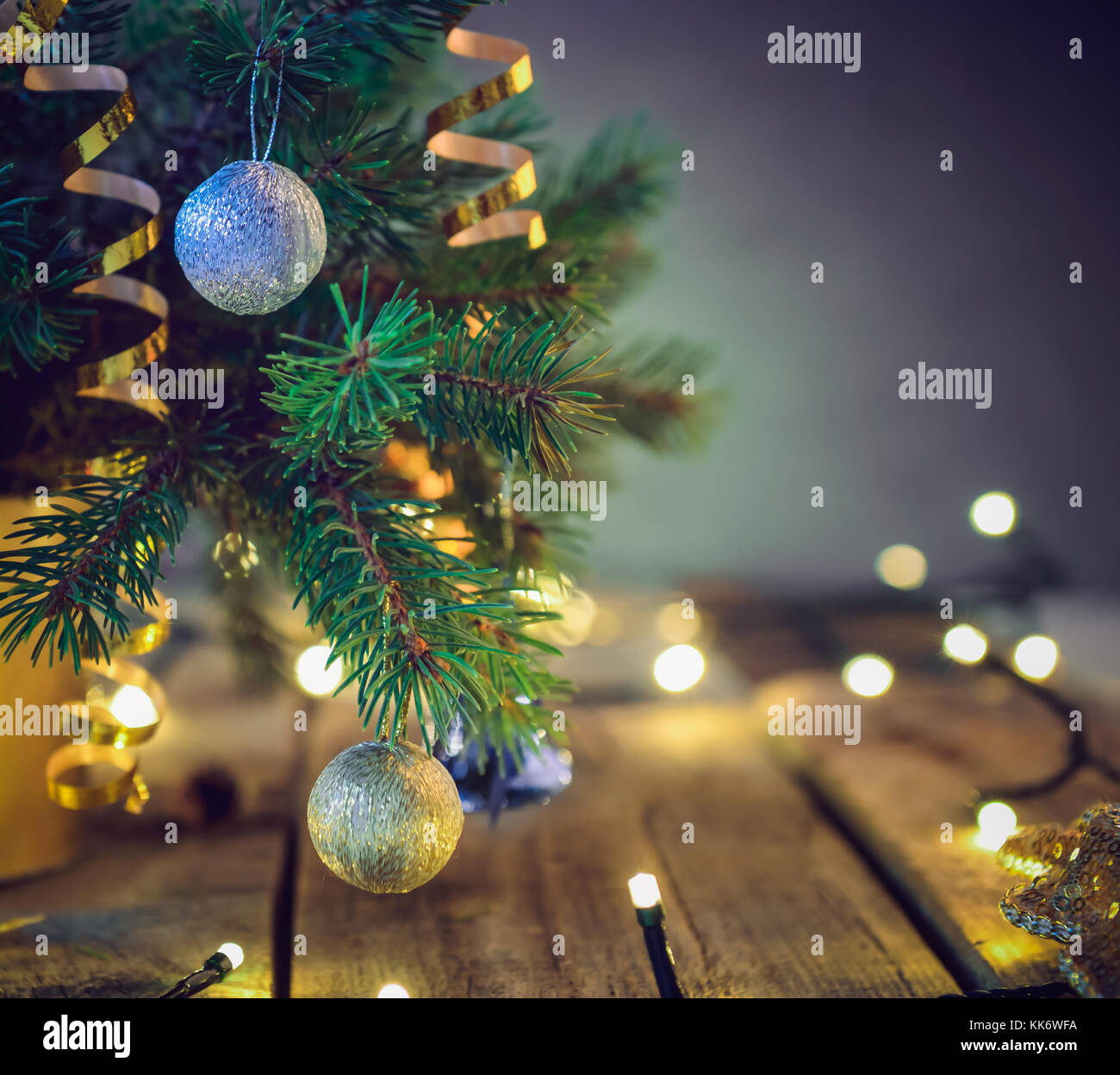 composition of christmas tree in vase with decorations and lights on the wooden vintage table retro style christmas background soft selective focus