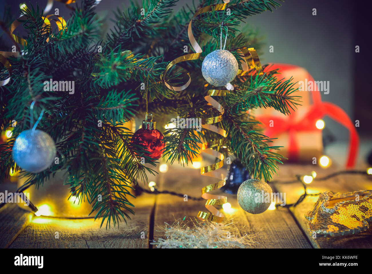 composition of christmas tree in vase with decorations gifts and lights on the wooden vintage table retro style christmas background soft selective