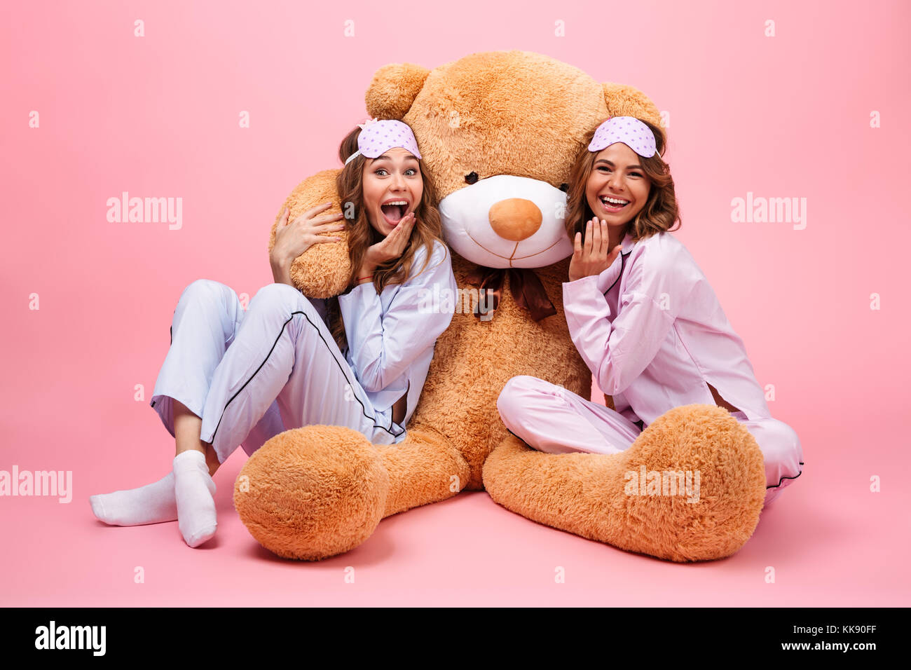 Two pretty cheerful girls dressed in pajamas sitting with a big teddy bear  and having fun isolated over pink 91f21c7b5