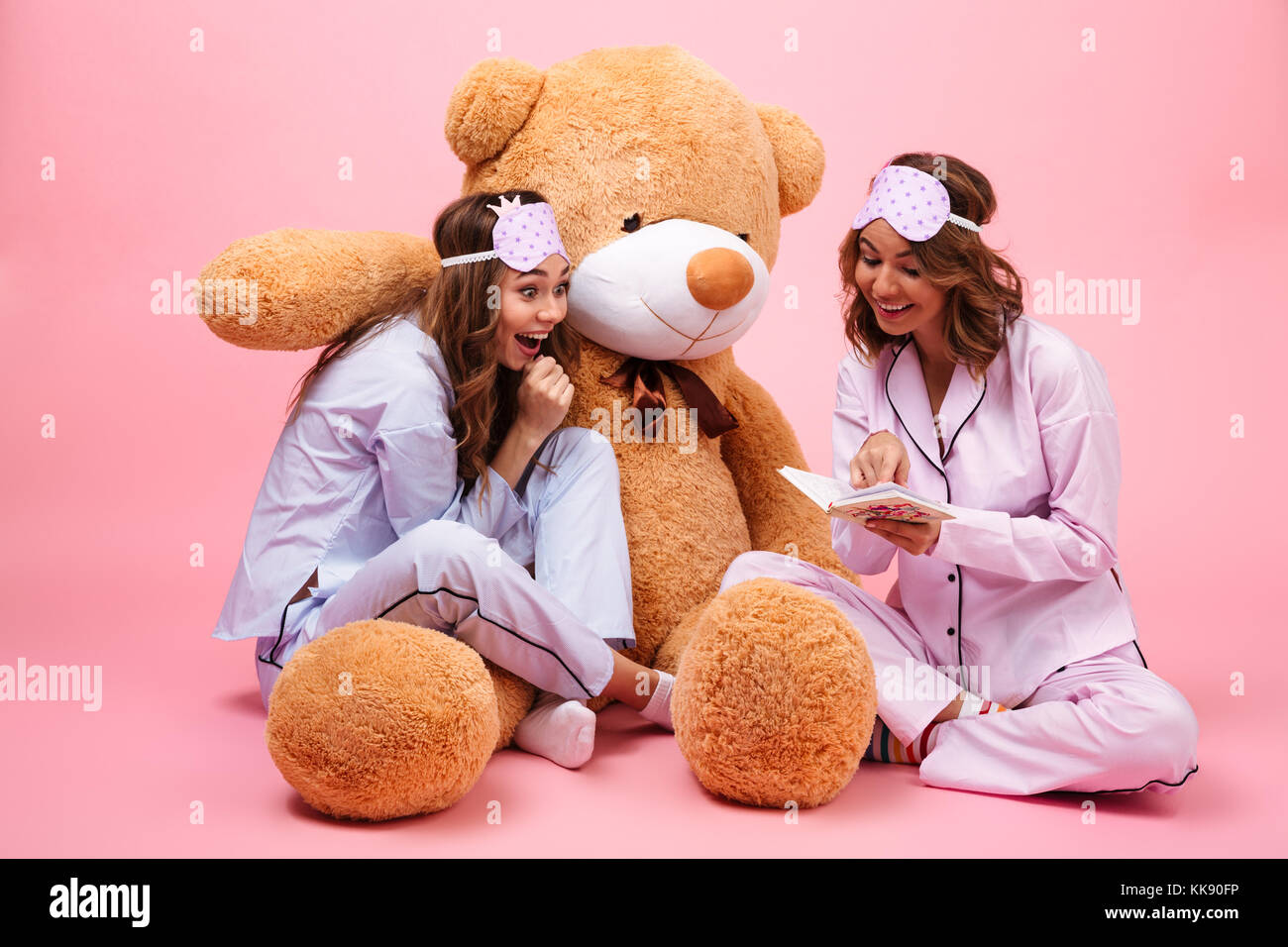 Two excited young girls dressed in pajamas sitting with a big teddy bear  and reading a book isolated over pink c50c92ca1