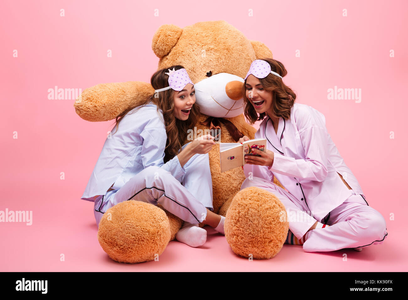 Two joyful young girls dressed in pajamas sitting with a big teddy bear and  reading a book isolated over pink 36bfb68e1