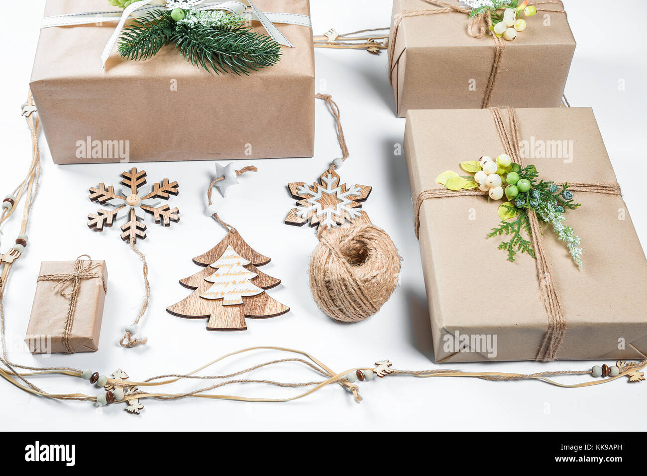 classy christmas gifts box presents in brown paper with toys and new year decor on white merry christmas card background