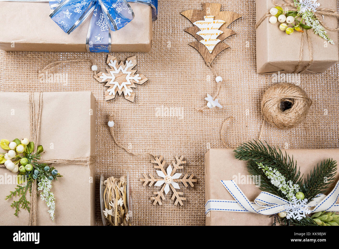 classy christmas gifts box presents in brown paper with toys and new year decor on burlap merry christmas card background