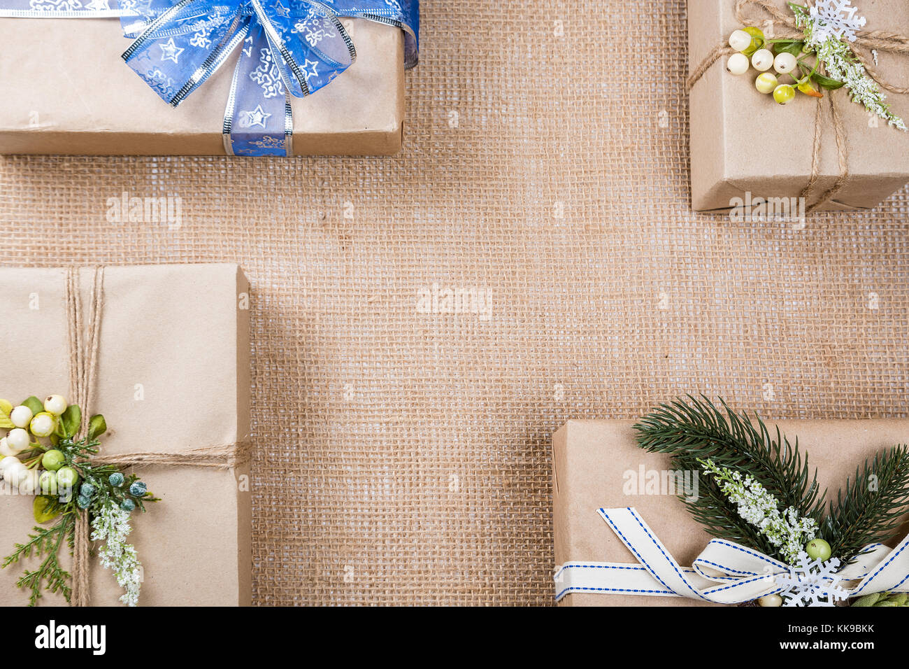 classy christmas gifts box presents in brown paper with bow and new year decor on burlap merry christmas card background