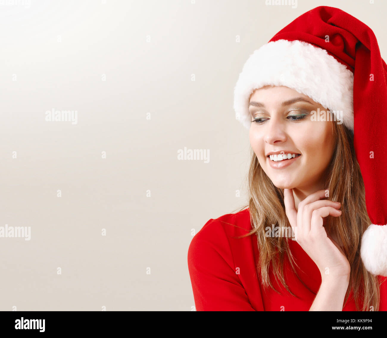 Cute young woman in Santa hat make a wish about Christmas gifts ...