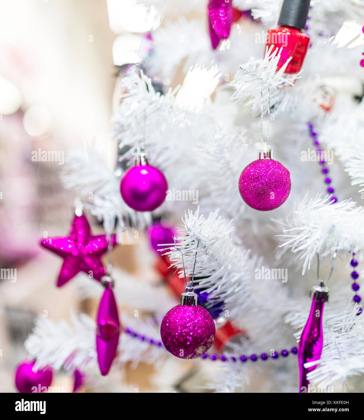 Purple baubles and decorations hanging on a white Christmas tree in ...