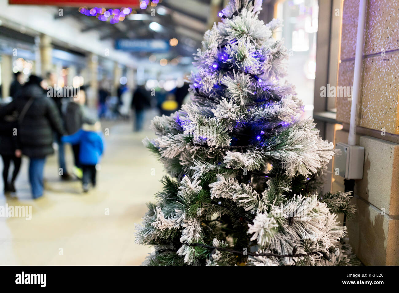 close up of an artificial christmas tree with blue twinkle lights and frost or snow in a shopping mall or shopping centre with people blurred in the b