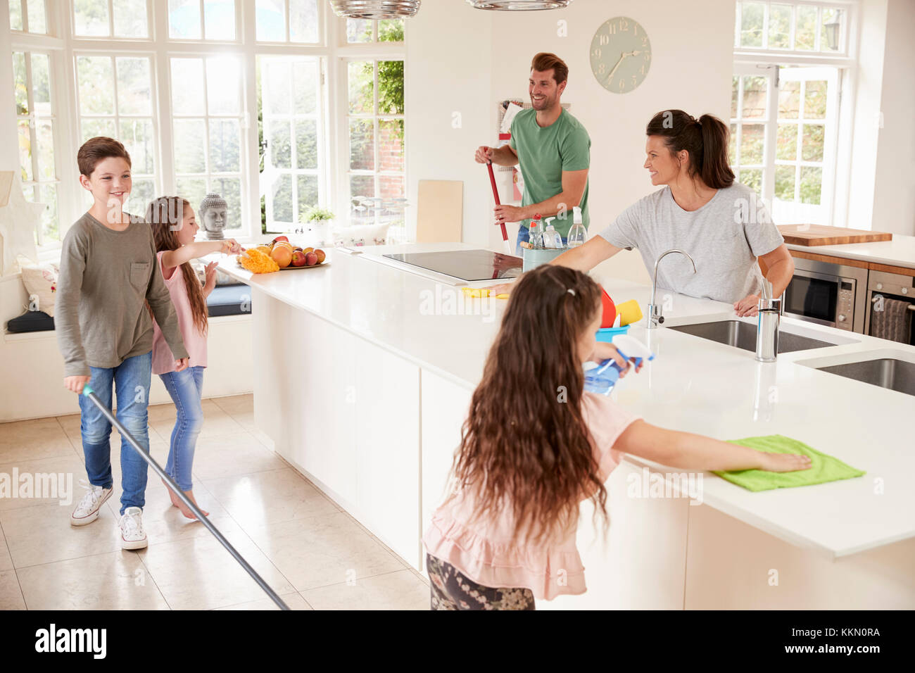 children helping parents with household chores in kitchen stock
