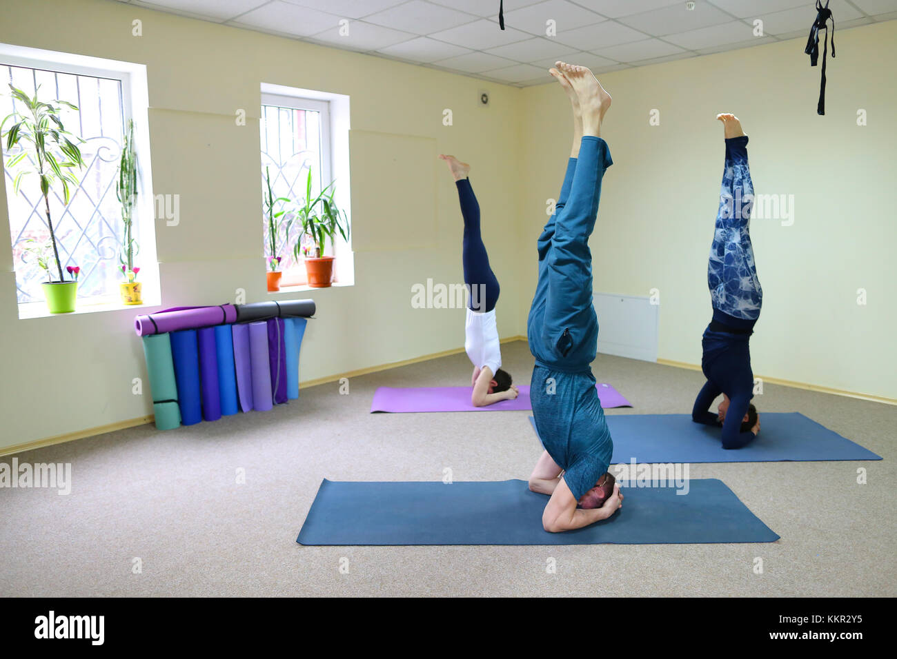 Two Women And Men Of American Appearance Engaged In Yoga People Sit