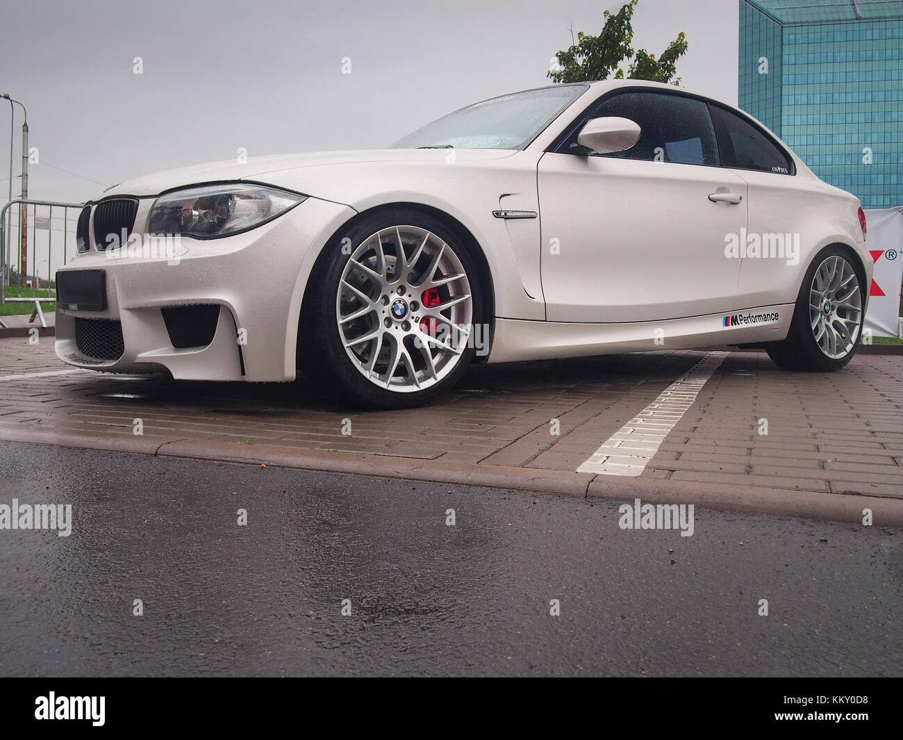 White BMW 1M In The Rain. This Model Is One Of The Most Popular Cars