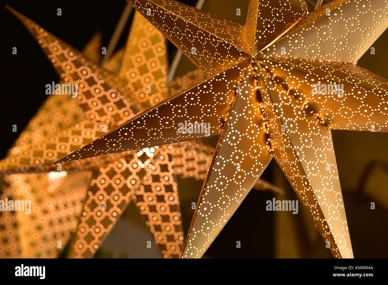 golden coloured christmas star decorations illuminated to celebrate
