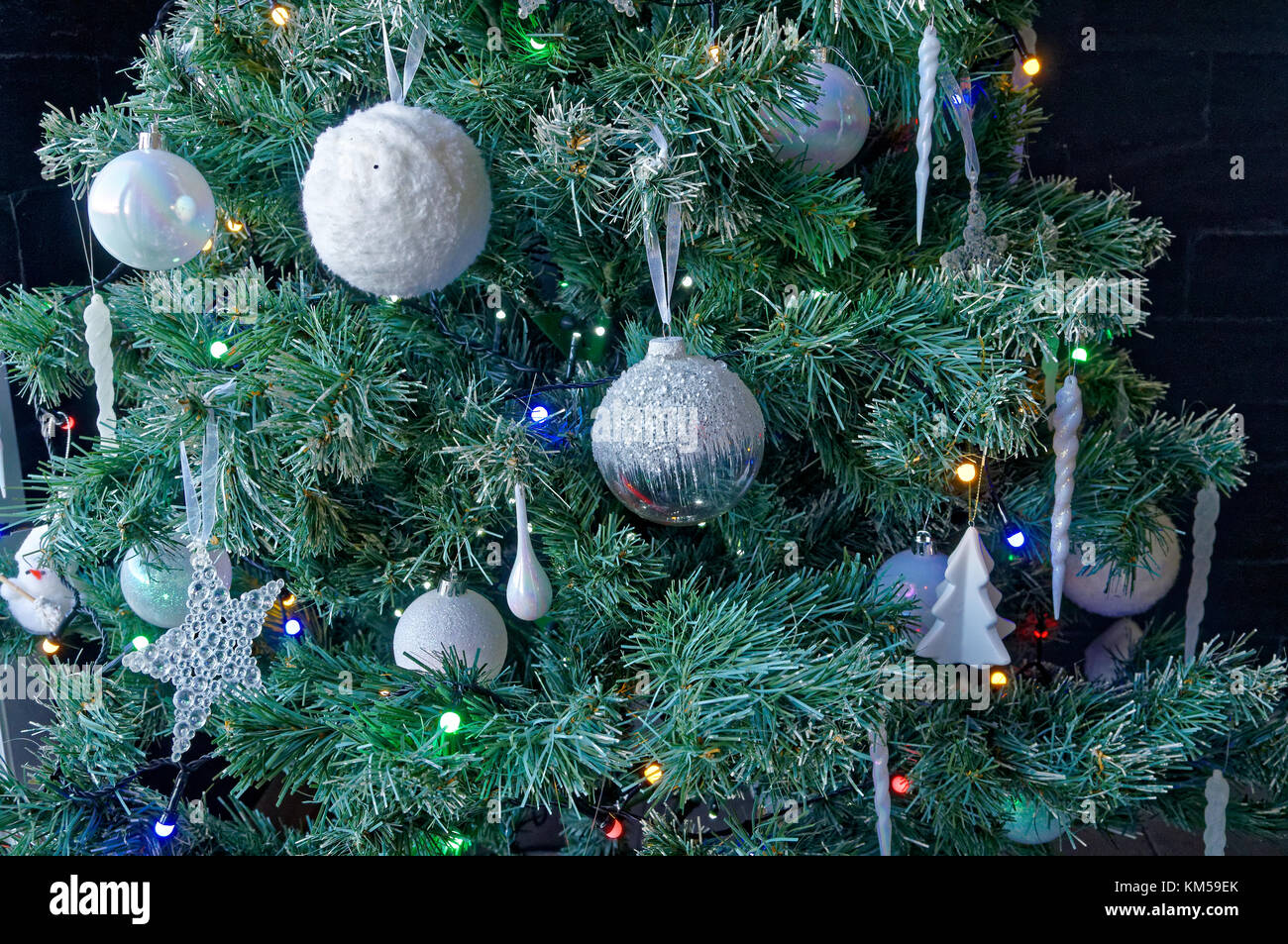 Closeup of white baubles and decorations with colored lights on an ...