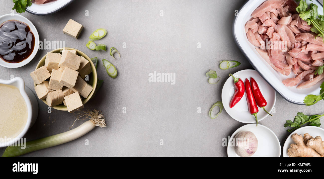 Asian cooking ingredients in bowls with tofu chili soy sauce meat asian cooking ingredients in bowls with tofu chili soy sauce meat ginger and broth on gray concrete background top view banner asian cuisine co forumfinder Images