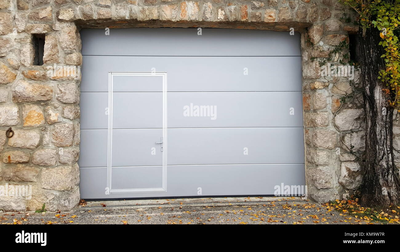 Modern Roll Up Metal Garage Doors With Integrated Smaller Inside Traditional Stone Wall Frame
