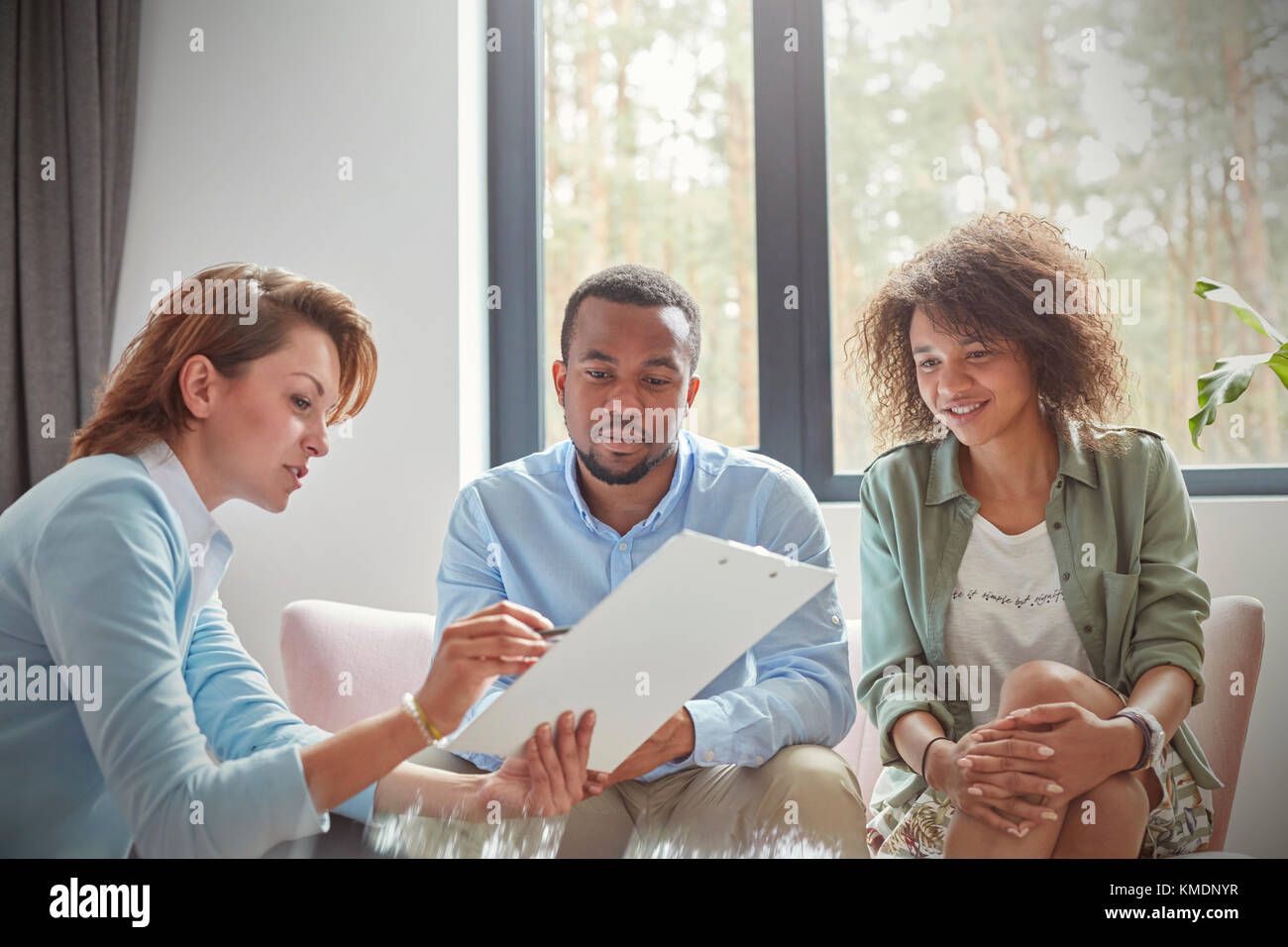 Female Therapist With Clipboard Talking To Couple In Couples Therapy