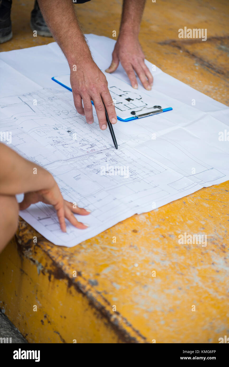 Architect discussing blueprint with construction worker at architect discussing blueprint with construction worker at building site malvernweather Gallery