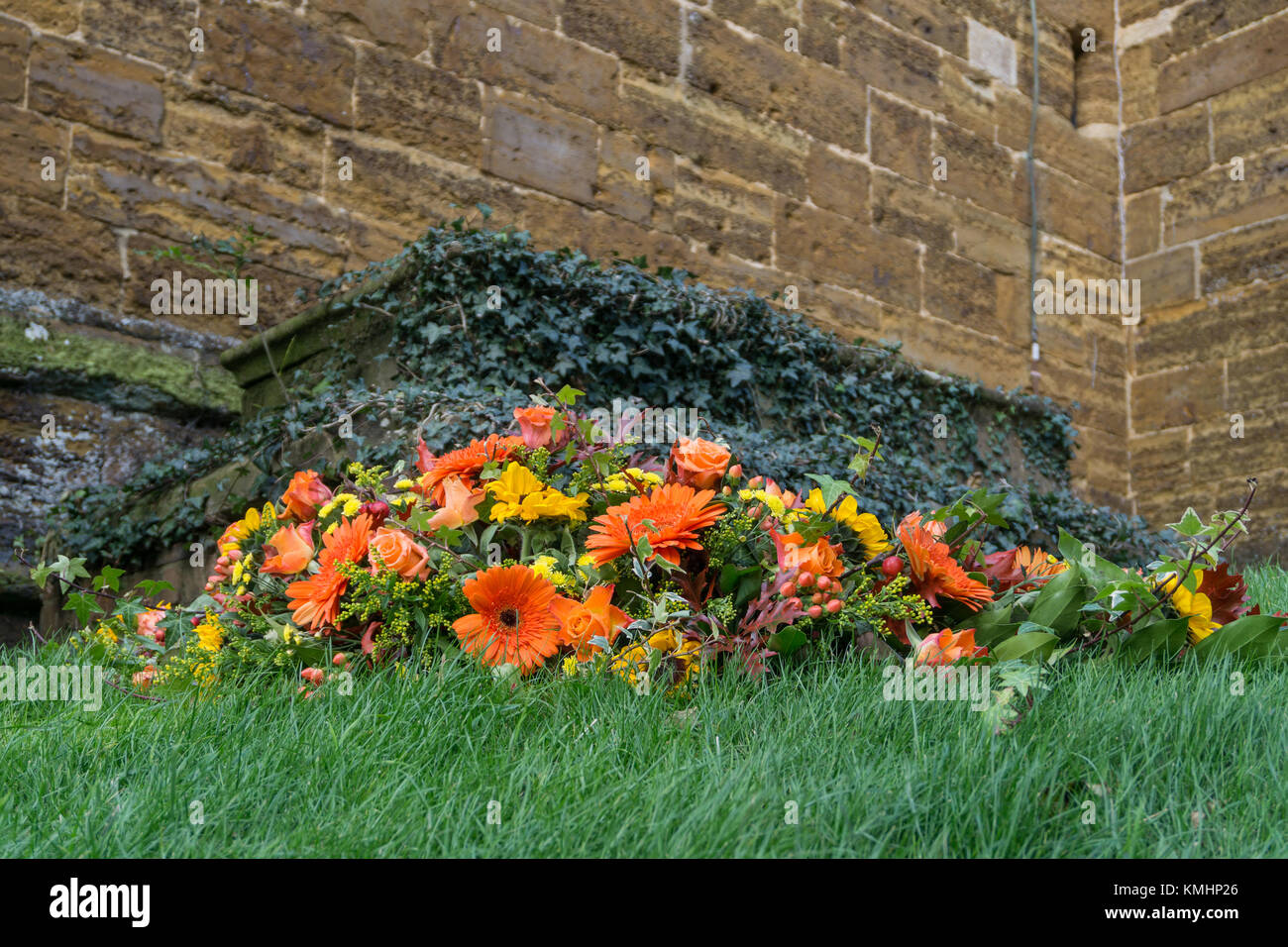 Large Wreath Of Orange And Yellow Flowers With An Old Ivy Covered