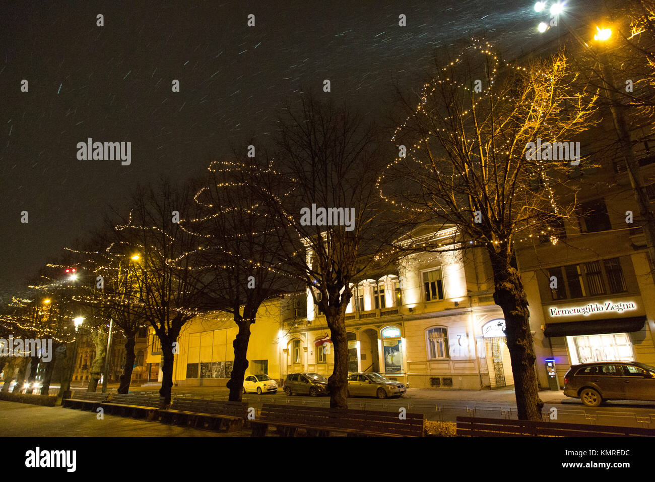 Snowfall at night in Riga, Latvia. A trees are decorated with Stock ...