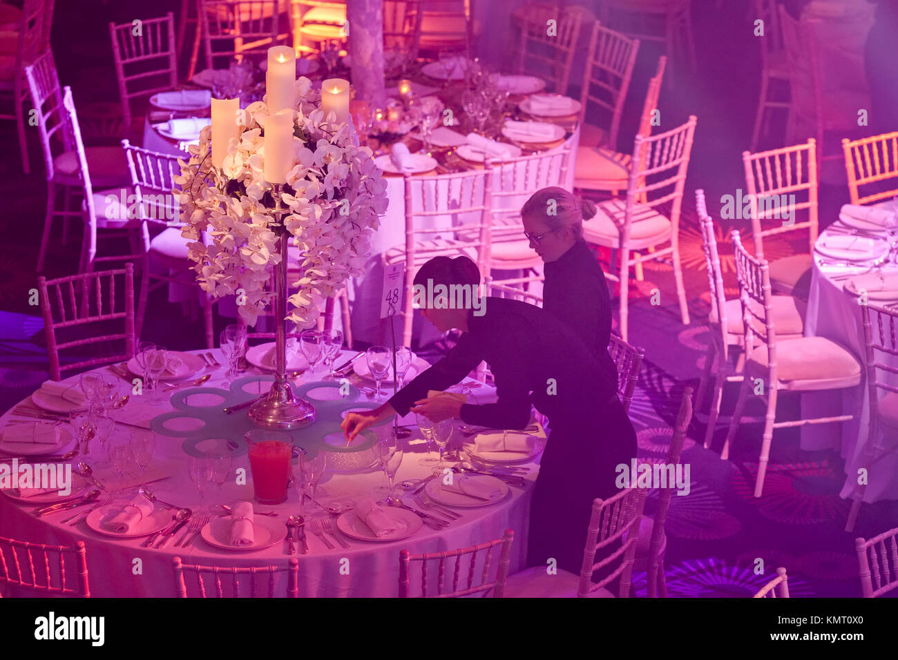 Staff preparing Table decorations at high end hotel wedding ...