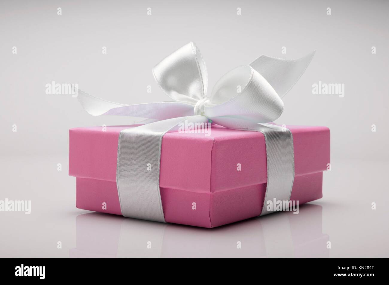 small pink box tied with a white ribbon Stock Photo: 167851400 - Alamy