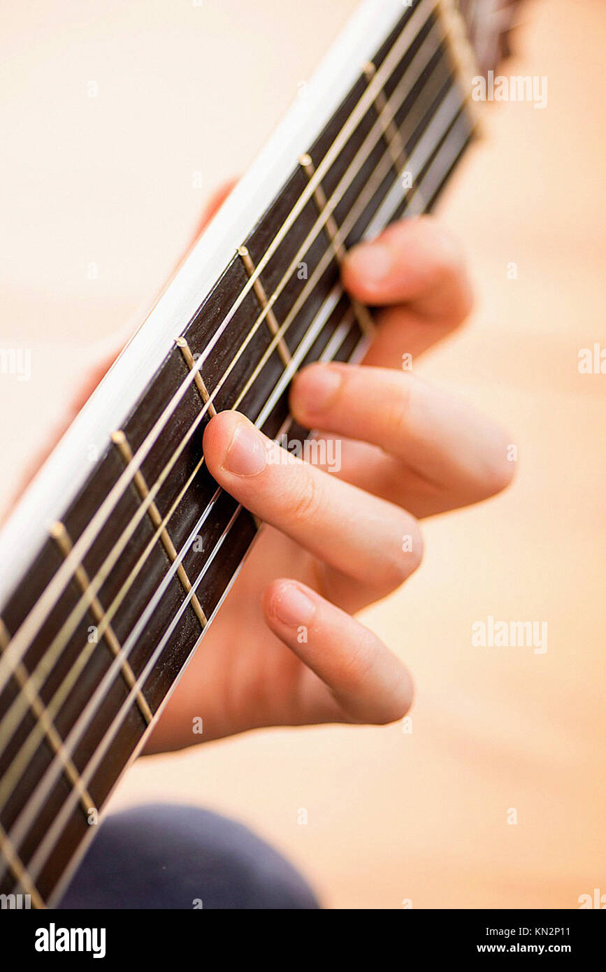 Strings And Fingers Of Young Man Playing A Chord On A Wooden