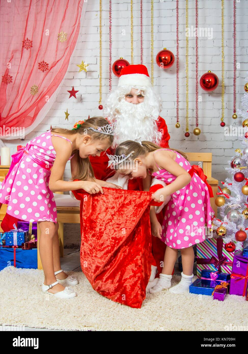 santa claus congratulates two girls sisters a happy new year and merry christmas in the home new years interior