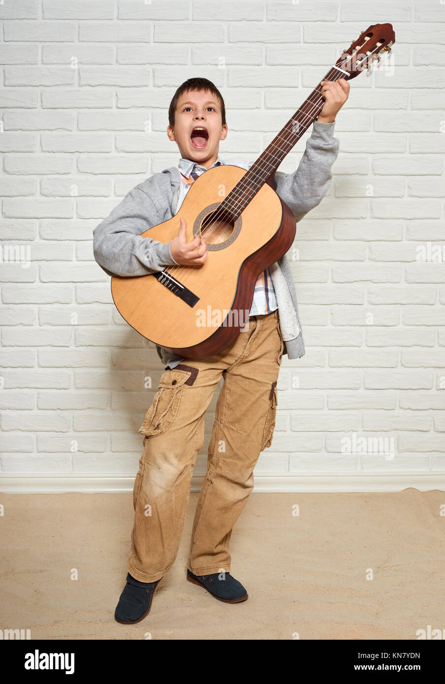 Boy Playing Music On Guitar Standing At Full Height White Brick Wall Background