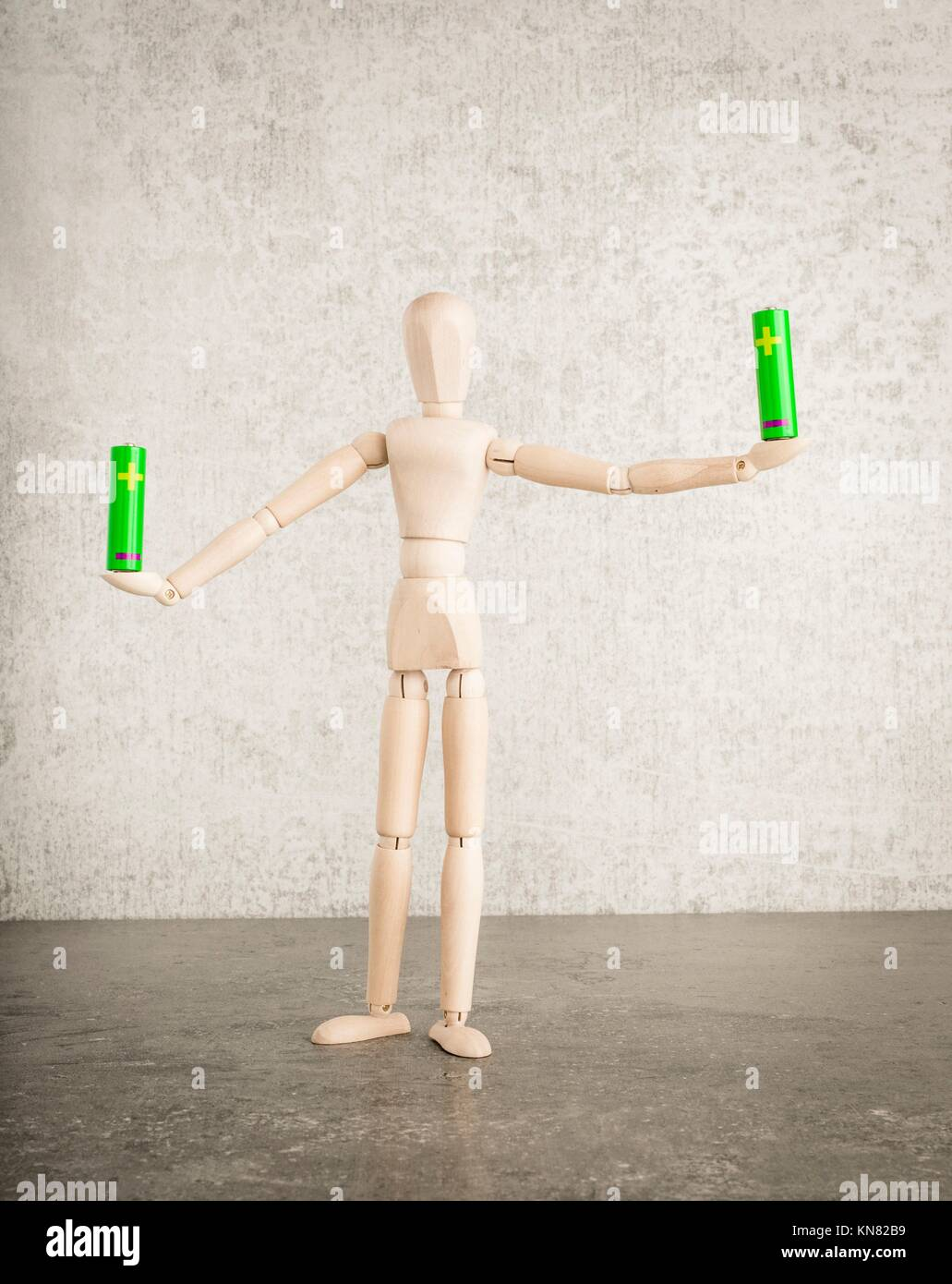 Electricity symbol stock photos electricity symbol stock images concept of green energy and power with wooden figure holding aa alkaline battery symbol of biocorpaavc Gallery