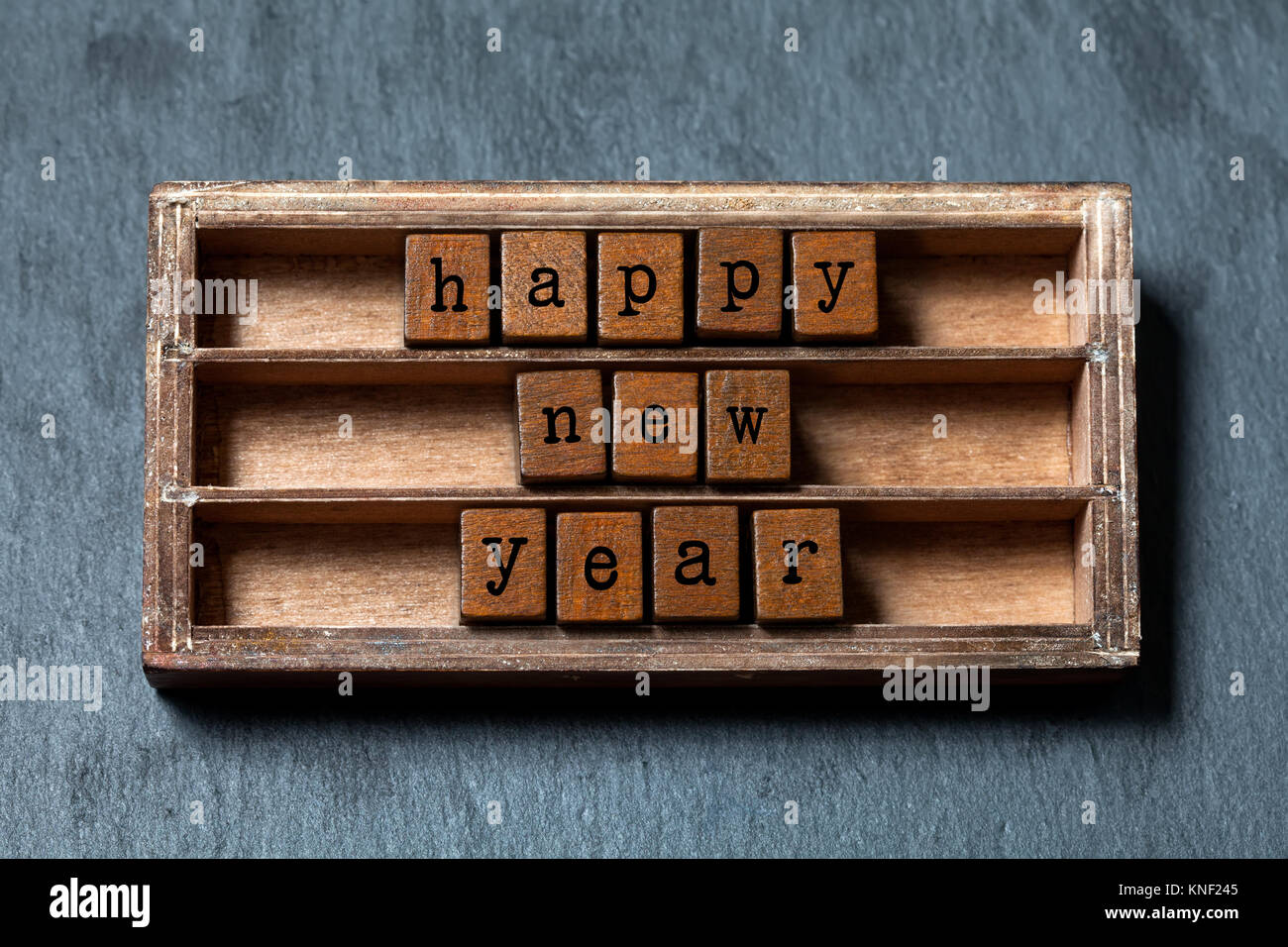 happy new year greeting card invitation poster vintage box wooden cubes with old style letters gray stone textured background close up soft focus