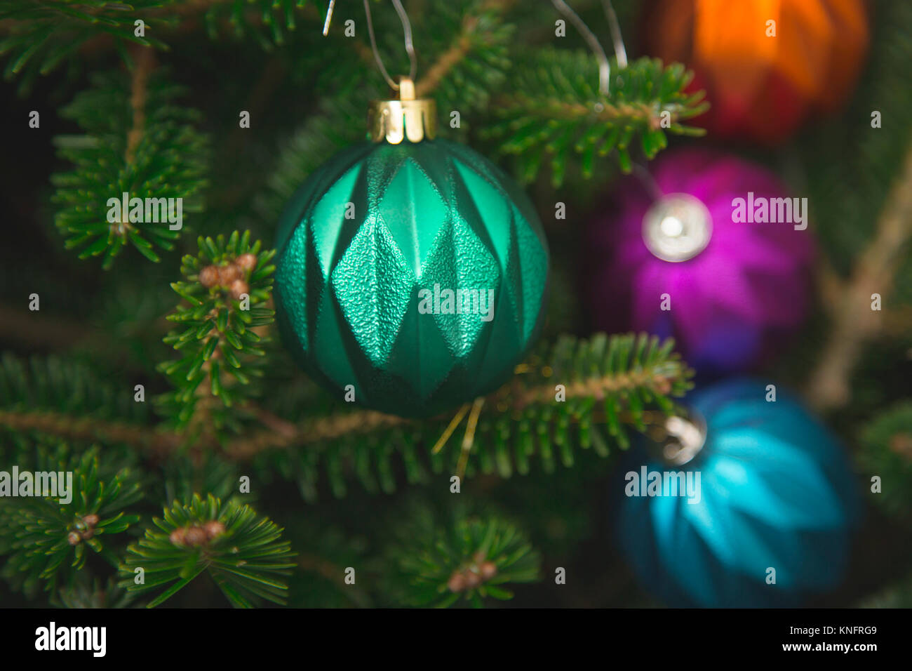a turquoise metallic bauble hanging on a fir tree branch and orange purple and blue baubles unfocused green new year or christmas backgroundclose u