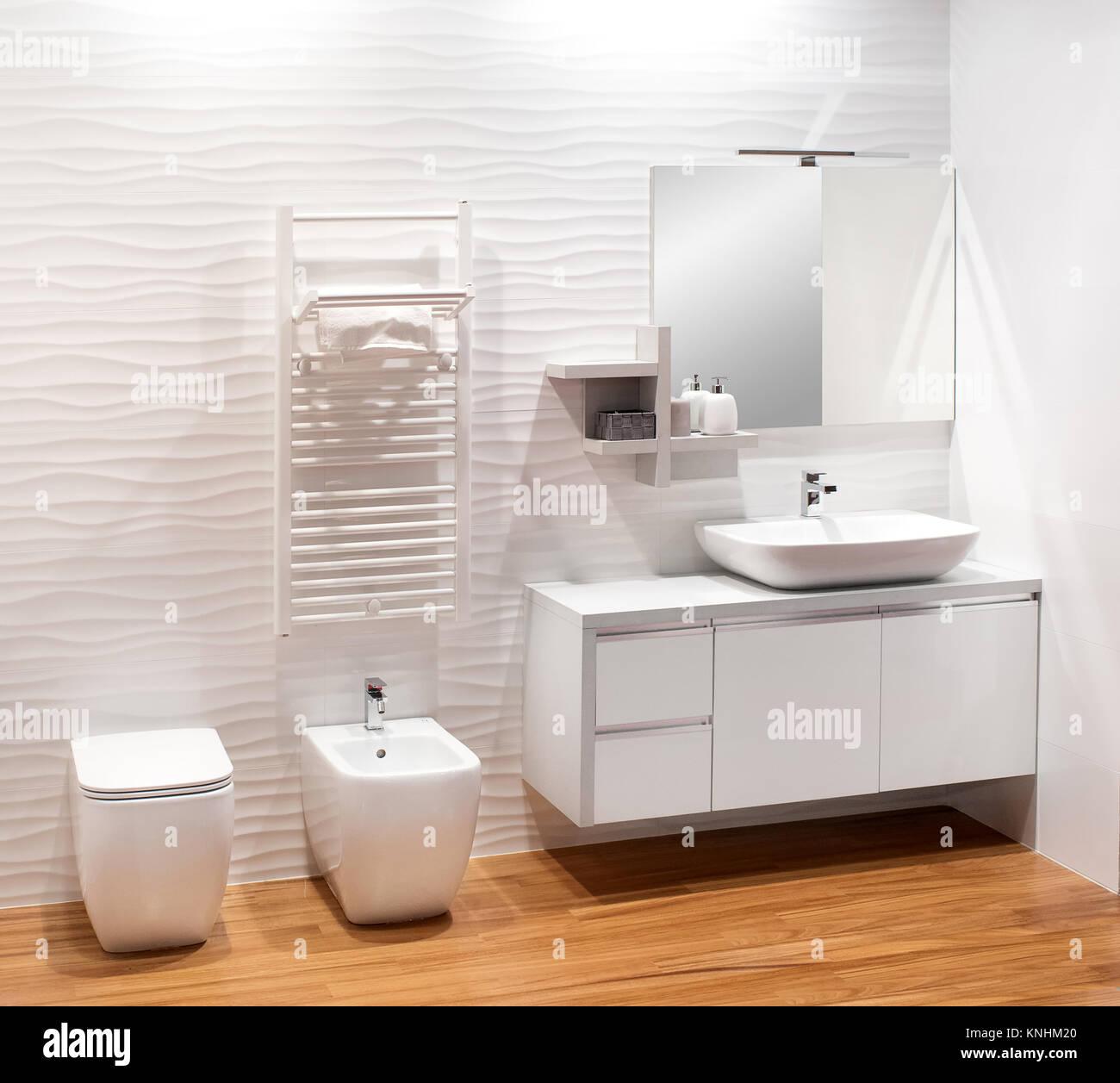 Plain monochromatic white bathroom with simple vanity cabinet, bidet ...
