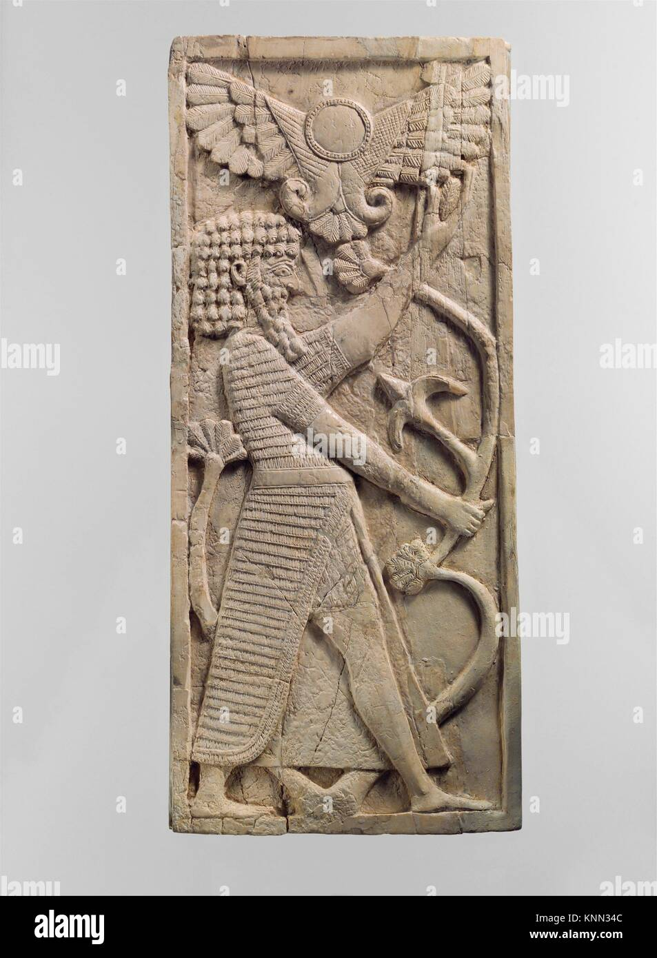 Furniture plaque carved in relief with a male figure grasping a