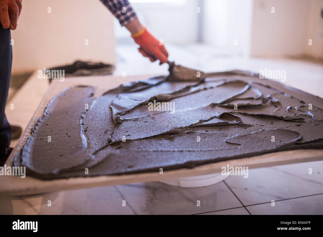 Laying ceramic tiles troweling mortar onto a concrete floor in laying ceramic tiles troweling mortar onto a concrete floor in preparation for laying floor tile dailygadgetfo Image collections