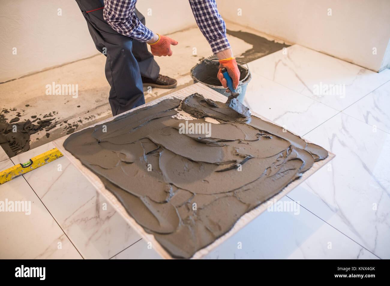 Cute 1 Inch Hexagon Floor Tiles Tiny 12 X 24 Ceramic Tile Round 12X12 Ceiling Tiles Home Depot 1930S Floor Tiles Youthful 2 X 6 Subway Tile Backsplash White3X6 Travertine Subway Tile Man Hand Troweling Adhesive For Ceramic Tile Flooring Stock Photo ..